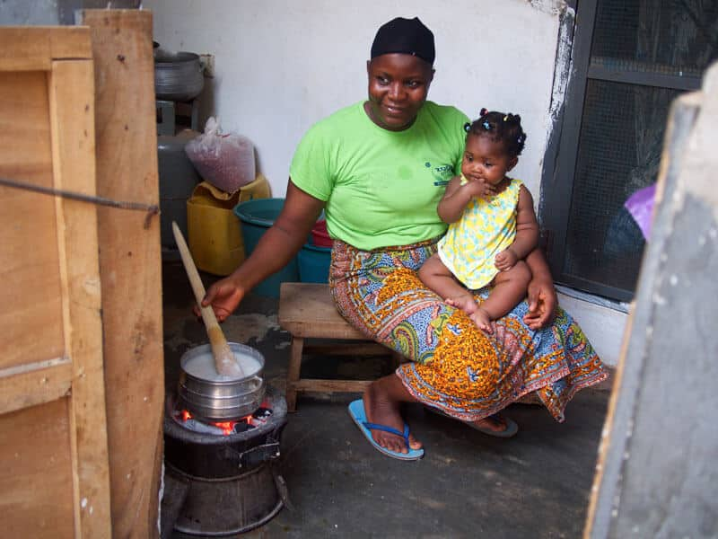 Aijat Alasha, a police officer, cooks on her Gyapa Cookstove, while taking care of her baby.
